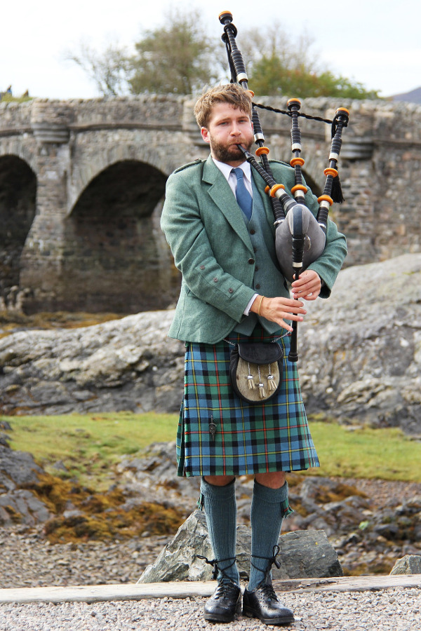 Man in traditional Scottish dress playing bagpipes in front of a stone bridge
