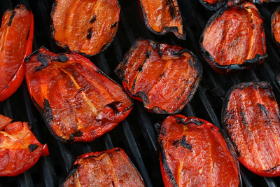 Charred red peppers on a barbeque