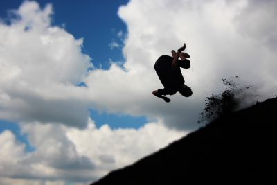 Silhouette of a man doing a somersault on a hill against a blue sky with puffy white clouds