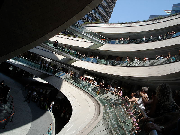 People standing along three levesl of curved balconies at Kanyon shopping centre in Istanbul
