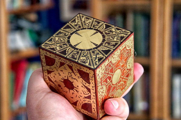 A hand holding the Lament Configuration, an ornate brown and gold puzzle box